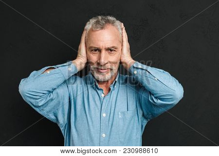 Image of irritated man 50s wearing shirt grabbing his head and covering ears due to annoying noise or unpleased dialog isolated over black background