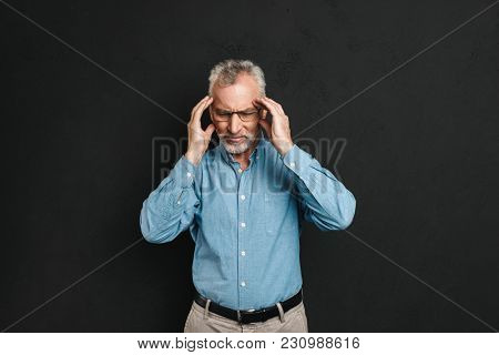 Image of old man 60s with grey hair and beard having headache and rubbing temples in fatigue isolated over black background