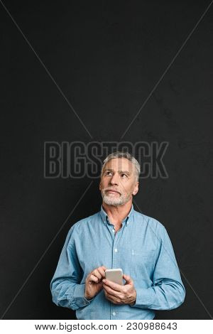 Photo of mature stylish man 60s with gray hair chatting or browsing internet on mobile phone and looking upward on copyspace isolated over black background