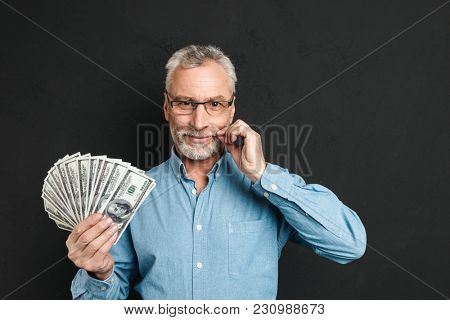 Image of middle aged rich man 60s with gray hair holding money fan of 100 dollar bills and touching his grey mustache isolated over black background