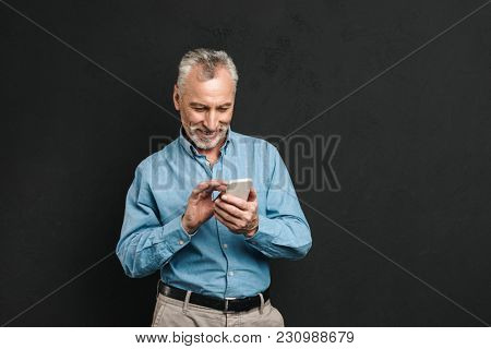 Photo of bearded male pensioner 60s with gray hair chatting or browsing internet on mobile phone isolated over black background