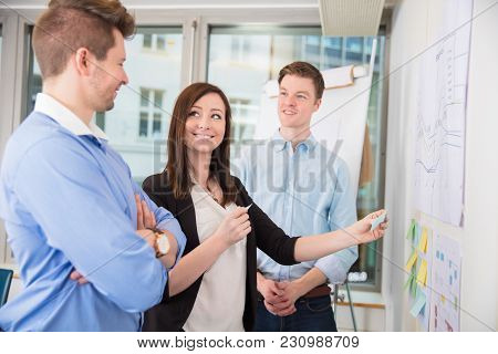 Smiling Businesswoman Sticking Adhesive Notes While Standing With Colleagues In Office