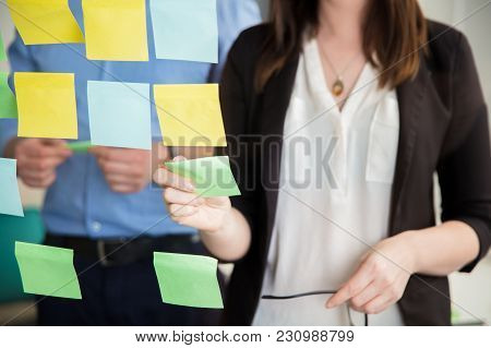 Midsection Of Businesswoman Sticking Adhesive Note On Glass By Executive In Office