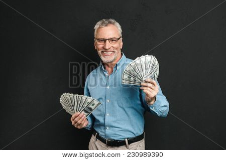 Image of rich good-looking adult man 60s with gray hair holding money two fans of 100 dollar bills and rejoicing his wealth isolated over black background