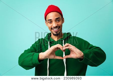 Portrait of a happy young afro american man in hat showing heart gesture with fingers at his chest isolated over blue background