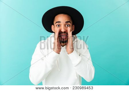 Portrait of a young afro american man in hat calling loud for someone isolated over blue background