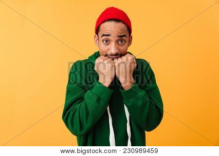 Portrait of a scared young afro american man in hat looking at camera isolated over yellow background