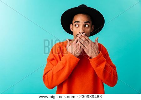 Portrait of a shocked young afro american man in hat looking away isolated over blue background