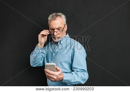 Image of serious mature elderly man 60s with gray hair looking on cell phone with pensive look while reading or scrolling news feed isolated over black background