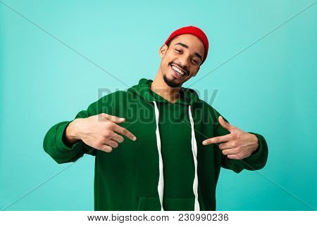 Portrait of a confident young afro american man in hat pointing finger at himself isolated over blue background