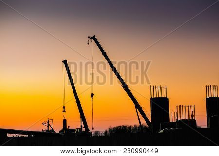 Crane And Building Construction Site On Background Of Sunset Sky. Industrial Landscape With Silhouet