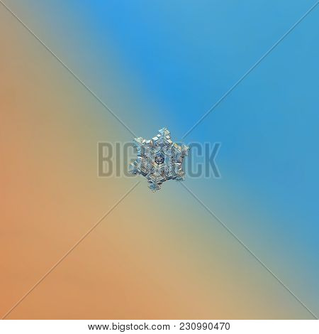 Snowflake Glittering On Blue Gradient Background. Macro Photo Of Real Snow Crystal: Small Sectored P