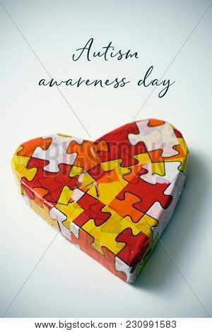 a heart patterned with many puzzle pieces of different colors, symbol of the autism awareness, and the text autism awareness day on a white background, with a slight vignette added