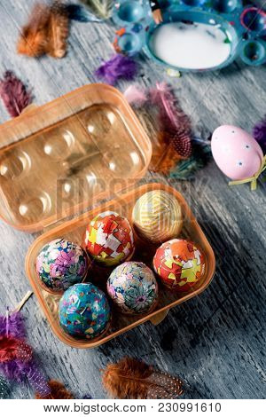 closeup of some homemade decorated easter eggs in a plastic egg box, and some other easter eggs on a gray rustic wooden table sprinkled with feathers of different colors