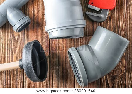 Plumber's items on wooden background