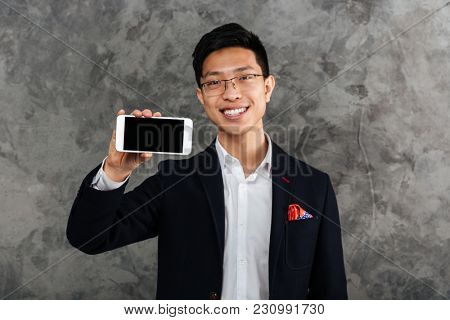 Portrait of a laughing young asian man dressed in suit showing blank screen mobile phone over gray background