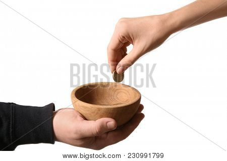 Woman putting coin into bowl in hand of poor man, isolated on white