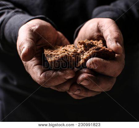Poor man holding pieces of bread, closeup