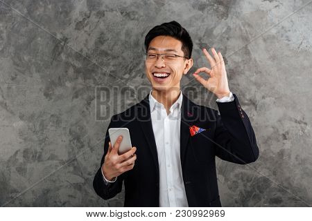 Portrait of a cheerful young asian man dressed in suit holding mobile phone and showing ok gesture over gray background