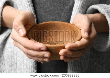 Poor woman with bowl and coins, closeup