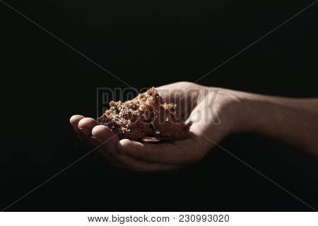 Poor woman holding piece of bread on dark background