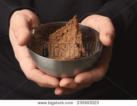 Poor man holding bowl with piece of bread, closeup