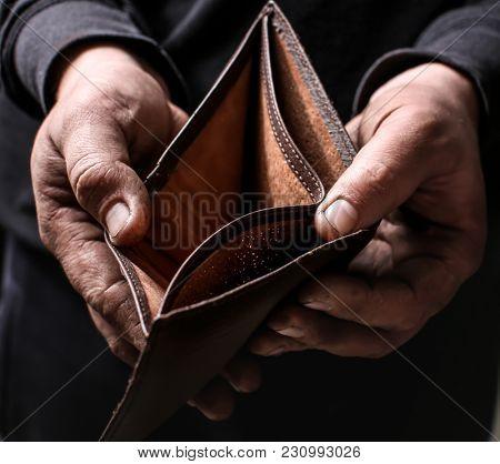 Poor man showing his empty wallet, closeup