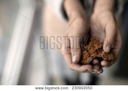 Poor woman holding bread on blurred background