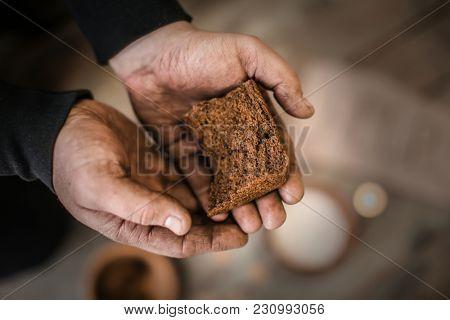 Poor man holding bread, closeup