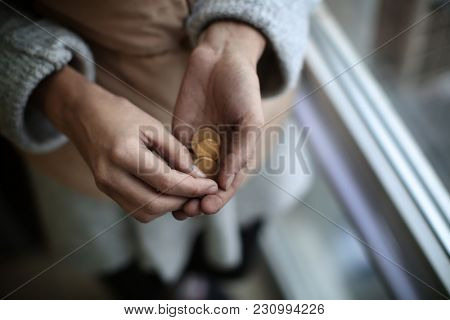 Poor woman holding coins, closeup