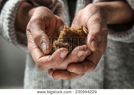 Poor woman holding piece of bread, closeup