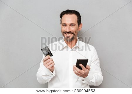 Portrait of a happy mature man dressed in shirt holding mobile phone and a credit card over gray background