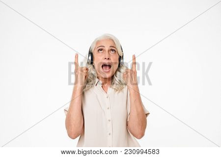 Retired female pensioner with gray hair listening to music using wireless headphones and pointing fingers upward isolated over white background