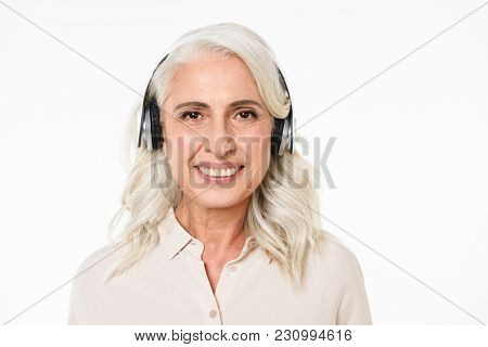 Portrait of adult gorgeous woman with gray hair smiling with perfect teeth and listening to music via wireless earphones isolated over white background