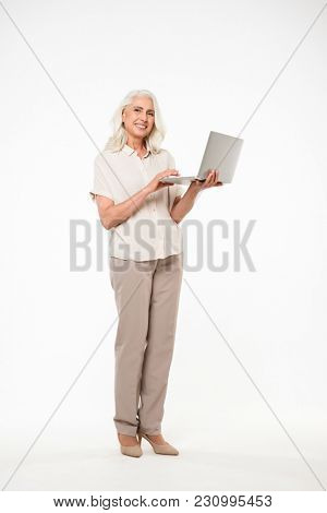 Full length image of mature adult granny 60s with gray hair smiling and holding silver laptop in hand isolated over white background