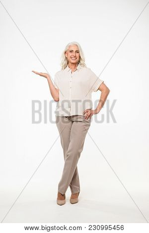 Full length portrait of adorable adult woman 70s with gray hair smiling and holding copyspace on palm isolated over white background