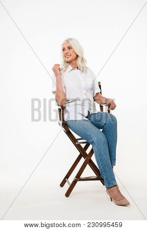 Full length portrait of elegant mature woman 70s with gray hair enjoying while sitting on wooden chair isolated over white background