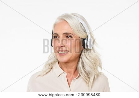 Photo of mature woman 60s with gray hair smiling with perfect teeth and looking aside while listening to music via wireless headphones isolated over white background