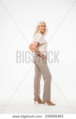 Full length portrait of beautiful adult woman 70s with gray hair smiling and looking on camera with arms in pockets isolated over white background