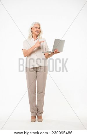 Full length image of adult woman with grey hair smiling and pointing finger on copyspace screen of laptop isolated over white background