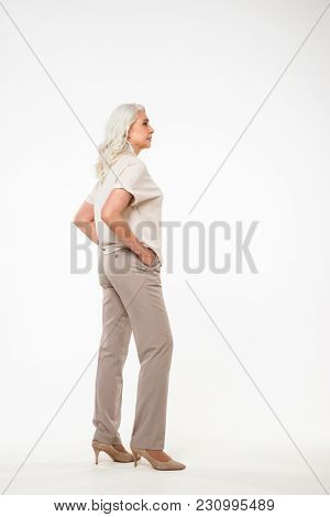 Full length portrait of beautiful adult woman 70s with gray hair and casual clothing looking aside with arms in pockets isolated over white background