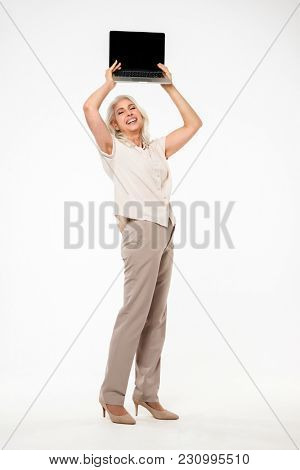 Full length image of late mature grandmother 60s with grey hair smiling and holding silver notebook above her head isolated over white background