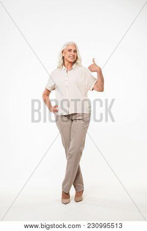 Full length portrait of smiling adult woman 70s with gray hair in casual showing ok sign on camera isolated over white background