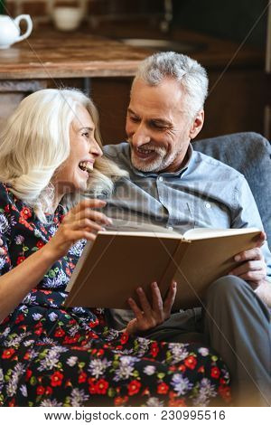Portrait of lovely old couple 60s resting together at cozy home while sitting on sofa and woman reading book with smile
