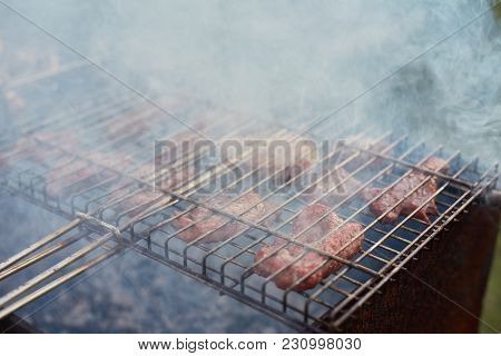 Barbecue In The Forest.shashlik At Nature. Process Of Cooking Meat On Barbecue, Closeup. Barbecue Wi