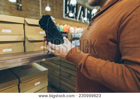 Man Seek Shoes In Store. Hold New Shoes In Hands