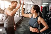 A beautiful girl and her well-built boyfriend are greeting each other with a high-five. They are happy to see each othr in the gym. Young people are ready to start their workout poster