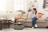 Desperate helpless woman sitting on sofa in messy living room. and talking on mobile, surrounded by many stack of clothes. Disorder and mess at home, copy space poster