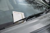 Parking ticket stuck on car windscreen for a penalty or fine poster
