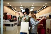 Technological concept. Two women in modern virtual reality headsets having expirience in shopping at lingerie store. Multiracial girls in vr glasses with bags touching and pointing interface elements in underwear shop. poster